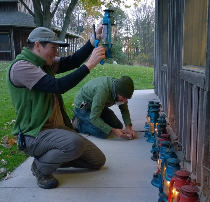 Merry Lea staff members light lanterns in preparation for the Enchanted Forest.
