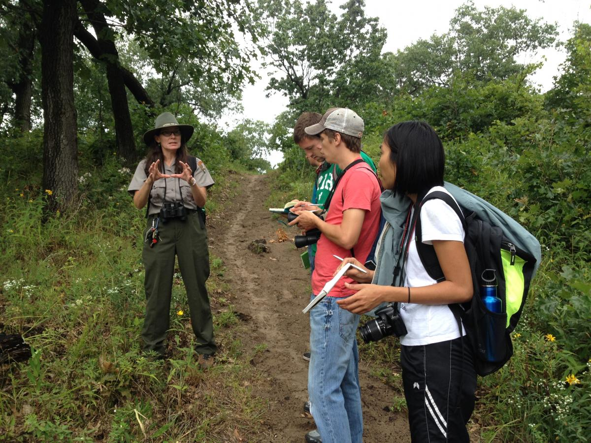 Three students with backpacks and notepads look towards a woman in a work uniform who talks to them. They are on a dirt path with green vegetation in the background.