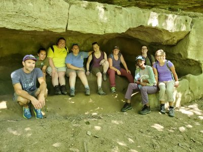 Ten students sit and smile at the camera underneath a large, tan rock that hangs over them.