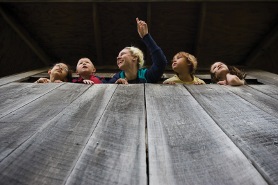 Looking up, you see a woman pointing to something in the distance and four children looking out. They are in a tower of gray, wooden planks.