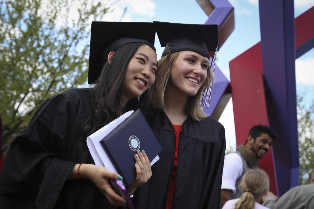 5_Celebration40_bys Two students in graduation caps and gowns at Goshen College graduation