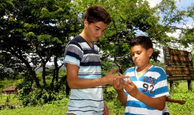 Monchito shows Alejandro how to wrap the string and hold the top.
