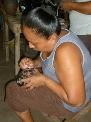 Azucena, wife of Juan Paulino, etches a design into a hand-made ceramic pot
