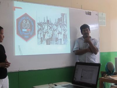 "Humberto showing the logo of the campaign and a photo of young brigadistas marching (with oversized pencils) in the ""war against illiteracy."""