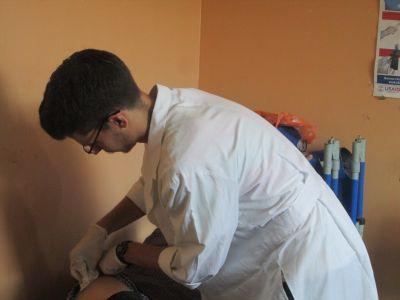 Luke tending a patient's wound