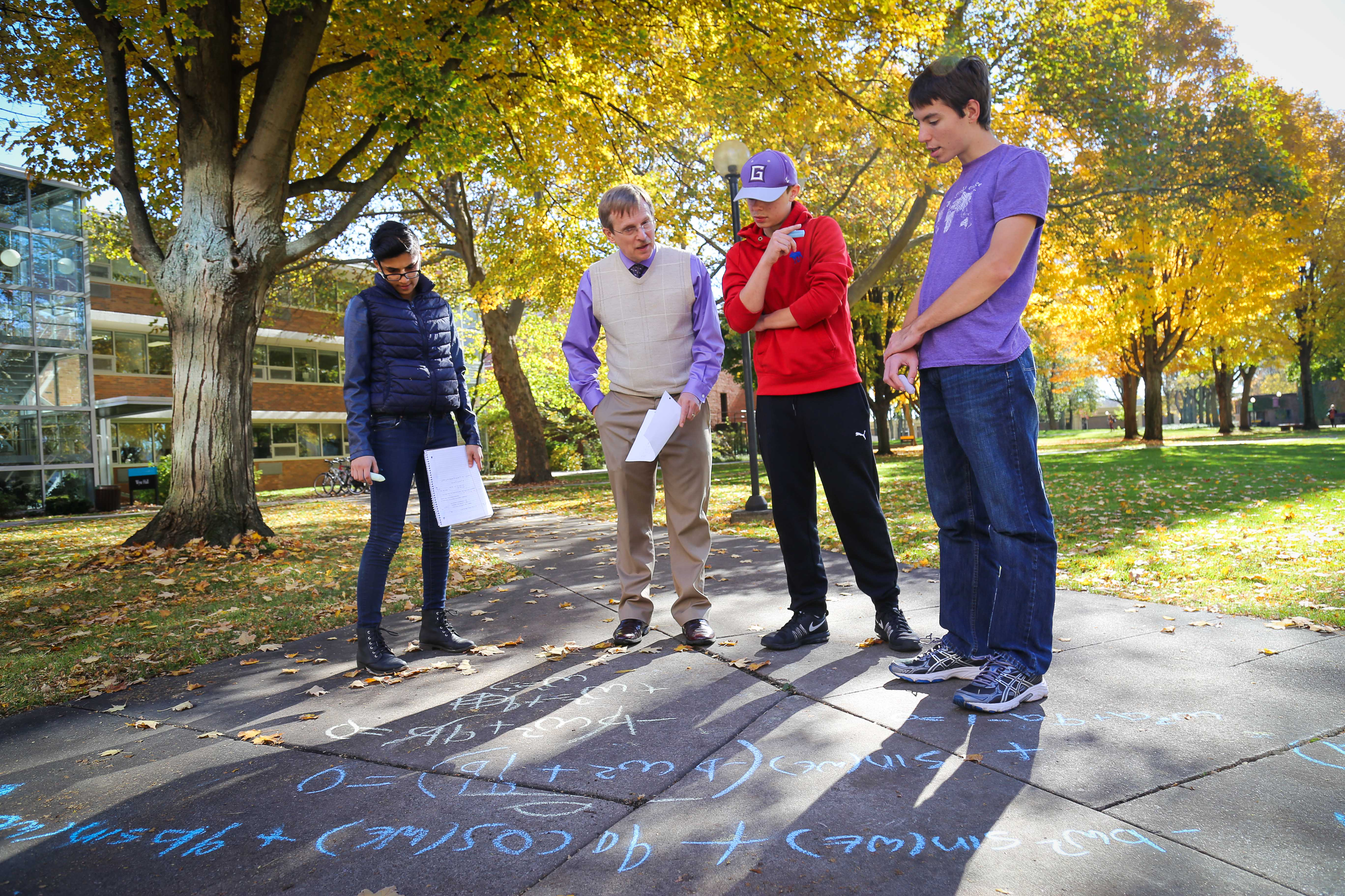 Math students with professor looking at equations on sidewalks