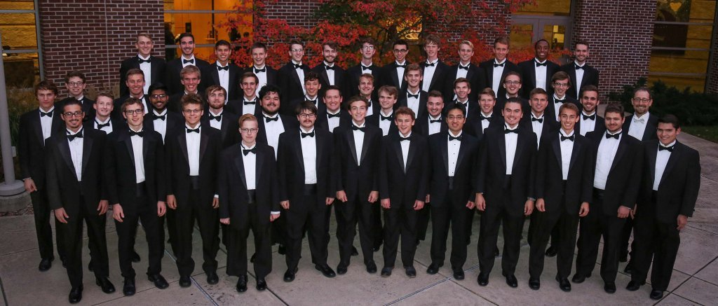 Men in formal dress posing together in three rows