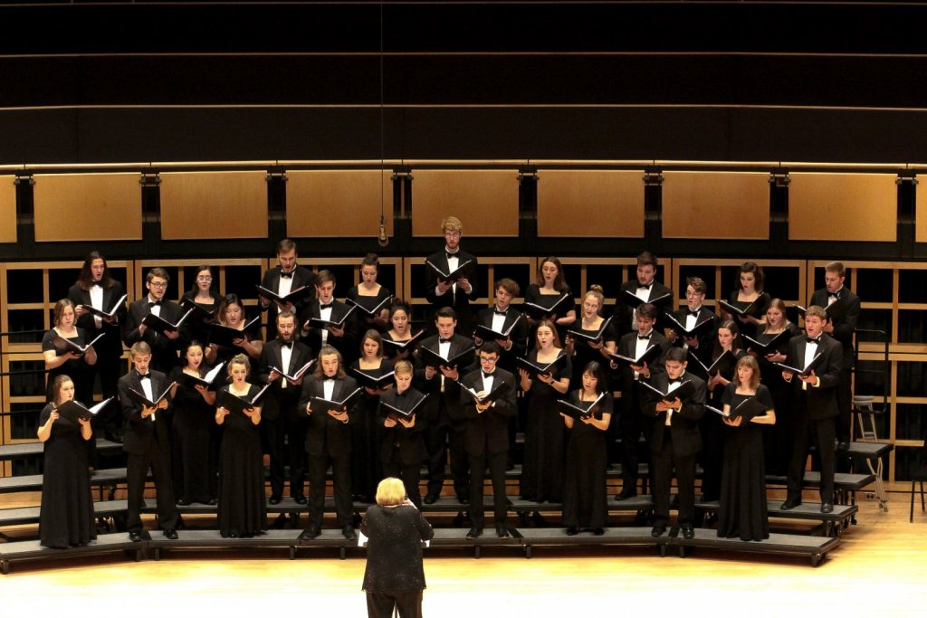 Choir dressed in black suits and dresses performing
