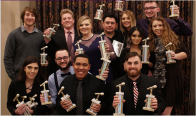 Students in formal clothing holding awards with microphones on top