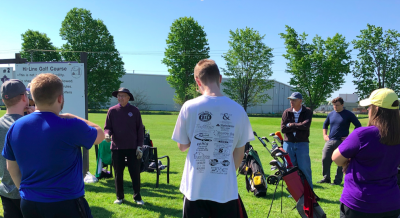Students at a golf course listening to a presentation