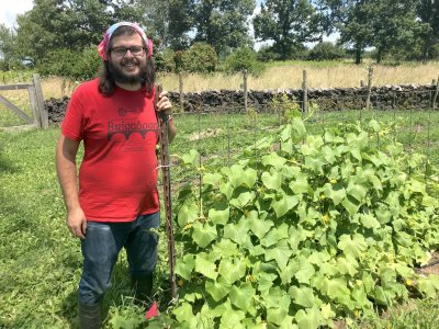 Stephen Lowe with a cucumber plant he trellised during the 2019 Agroecology Summer Intensive.