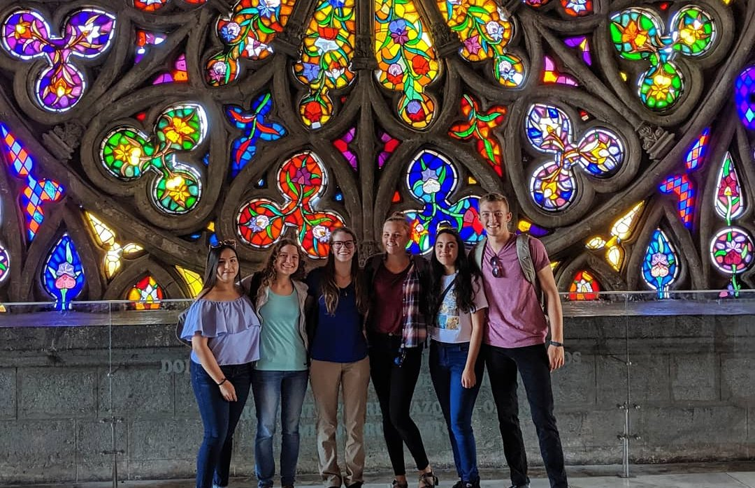 Six students posing together in front of a stained glass basilica