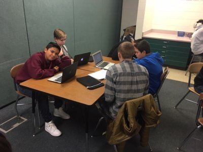 Middle school students sitting at a desk working on laptops