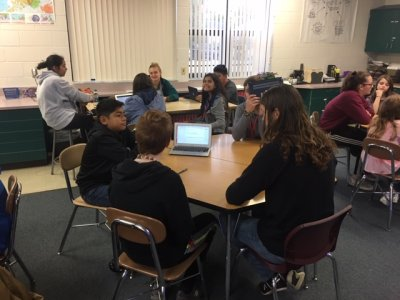 Middle School students working in a classroom at a hexagon table
