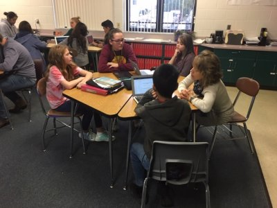 Middle Grade Students working at a hexagon table