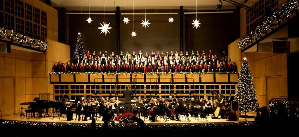 Choir performance in Sauder Concert Hall with Christmas decorations