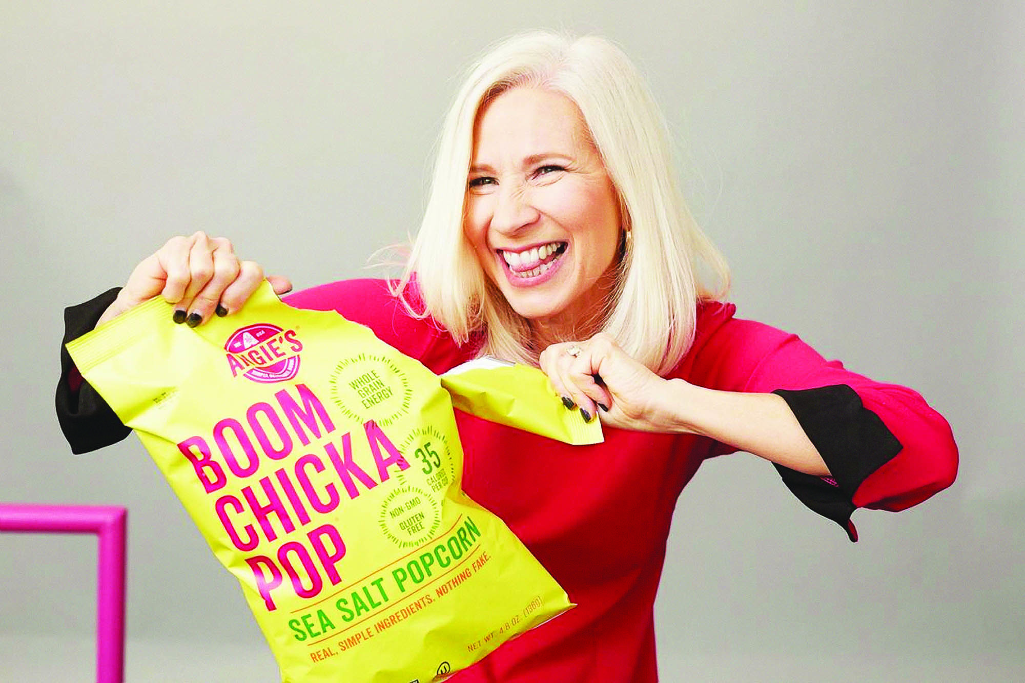 Woman in a fuchsia long sleeve shirt smiling while tearing open a bag of 'Boom Chicka Pop' popcorn
