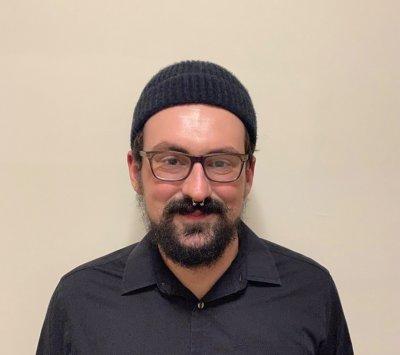 Man in black shirt, black winter hat, glasses, smiling