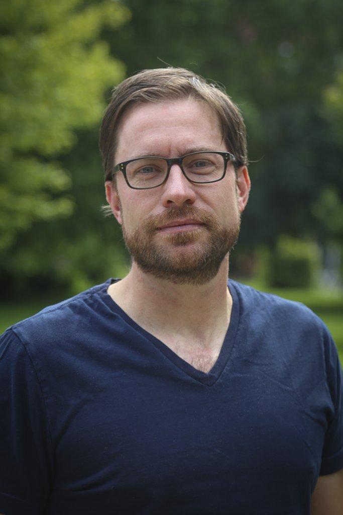 Man in dark blue shirt smiling