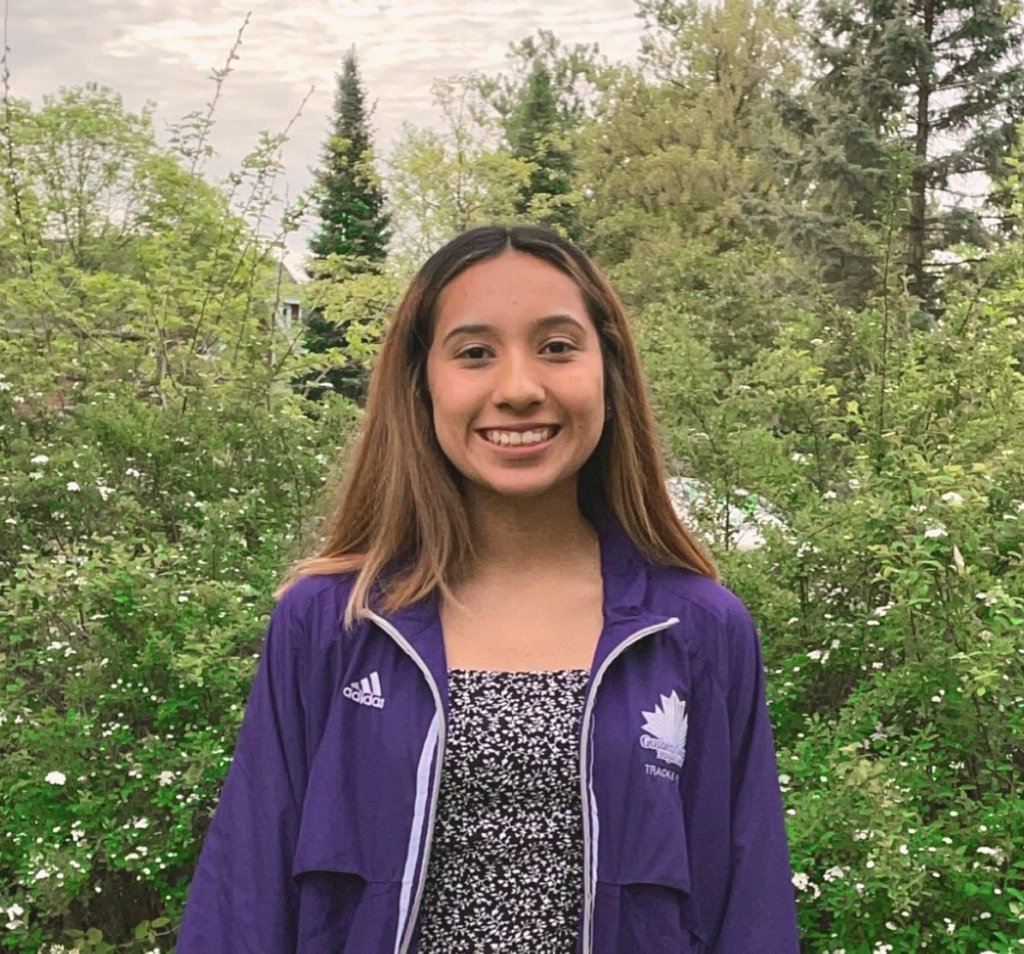 Woman in purple jacket with Goshen College track logo smiling