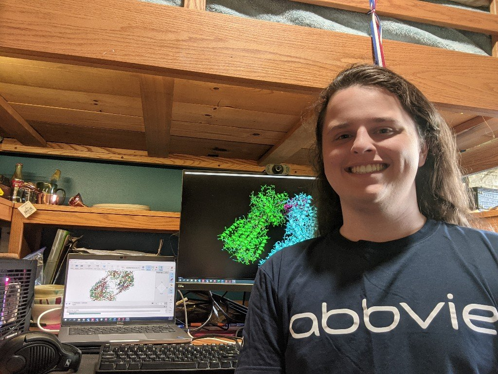 student smiling in front of a computer, wearing black shirt with