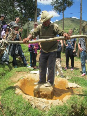 Jacinto shows how he rocks the mill stone back and forth to grind the ore into a fine powder