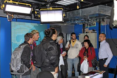 GC students listen to a news producer in an RPP television studio.