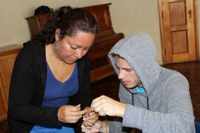 Eliana helps Alan with his bracelet.