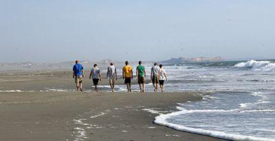 Goshen College men stroll down the beach.