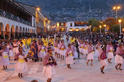 A large group of women sing and dance their way by the Plaza de Armas.