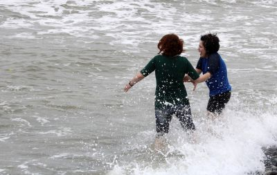 A wave surprises Sierra and Edith.