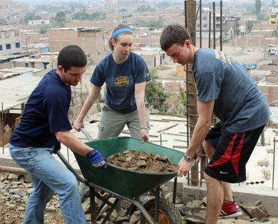 Brian, Leah and Joel lift a rock-laden wheel barrow.