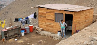 A mother of two stands beside her newer home in Puente Piedra.