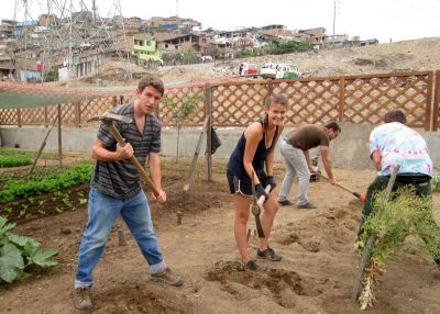 Micah, Jo and Ike take their turn at working the sandy soil in a Villa Maria community garden.