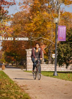 Student riding a bike on the Goshen College campus.