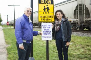 "Glenn Gilbert (left), sustainability coordinator at GC, and Gretchen Geyer (right), a senior from Parnelll, Iowa, who initiated the project, pose with the newly-installed ""no idling"" sign on the GC campus."
