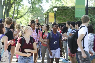 """New students make their way through the annual """"applause tunnel"""" following the opening convocation at Goshen College on Wednesday, Aug. 27. (Photo by Brian Yoder Schlabach/Goshen College)"""