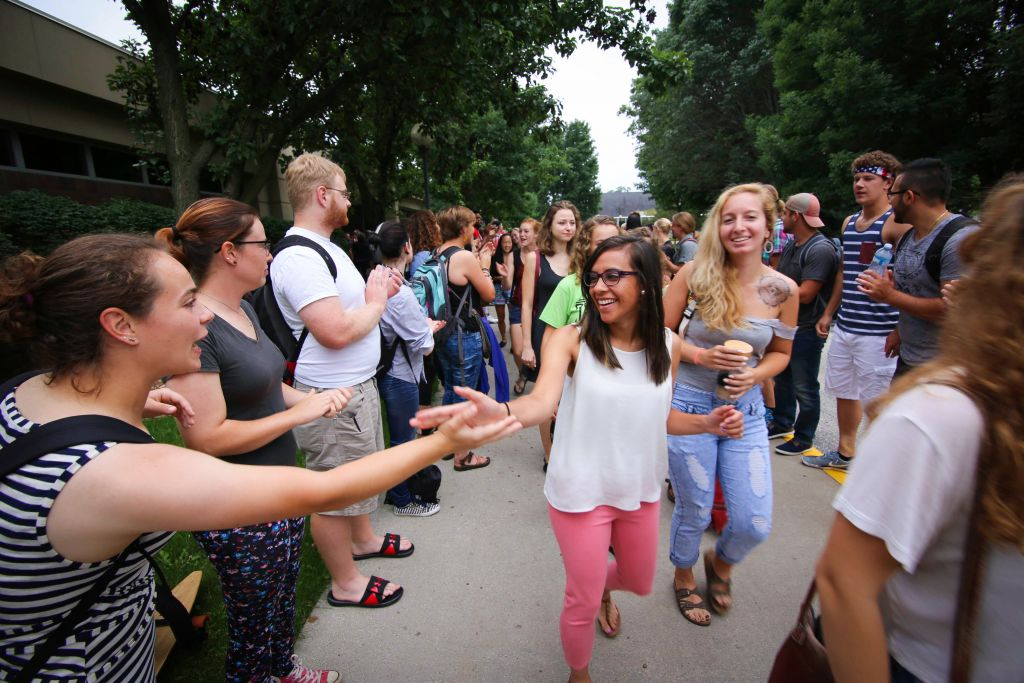 Janeth Vela (center), a senior from Goshen, high-fives Molly Zook (left), a senior from Doylestown, Ohio, during the annual applause tunnel following the opening convocation. Brynn Godshall (right), a senior from Lancaster, Pennsylvania, looks on. The applause tunnel tradition is a way to welcome new and returning students.