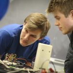 Students working among wires and circuits