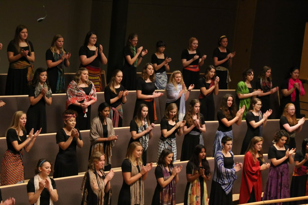 Women's World Choir clapping to one of the songs they are performing.