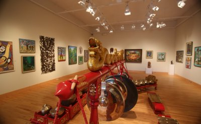 the Gamelan in the middle of an art gallery that is full of paintings on the wall.