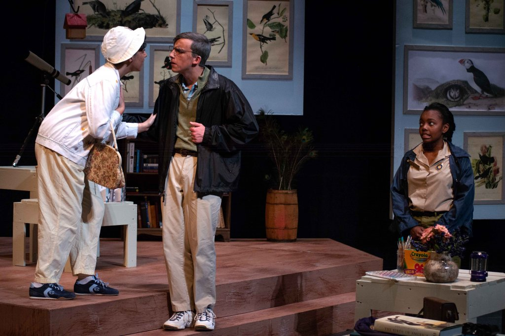 Three students acting; two as older people, talking to each other on the steps that make up a large part of the set, while the other actor watches their exchange.