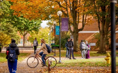 Students walking and biking to class and talking to each other while surrounded by colorful leaves on the branches and ground.