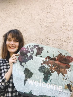 Woman smiling while holding a GC poster that layouts the world.