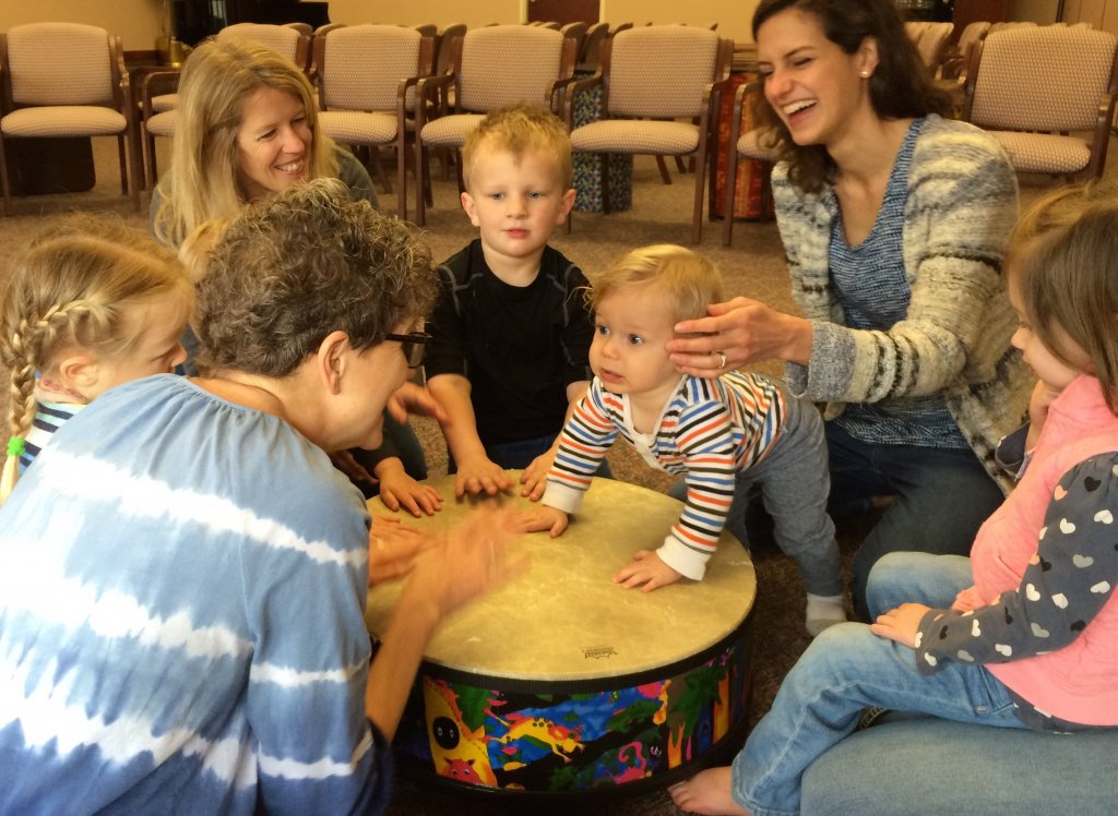 Moms and toddlers paling on a large drum in the middle of their circle.