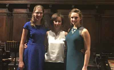 Two female students stand with their violin teacher
