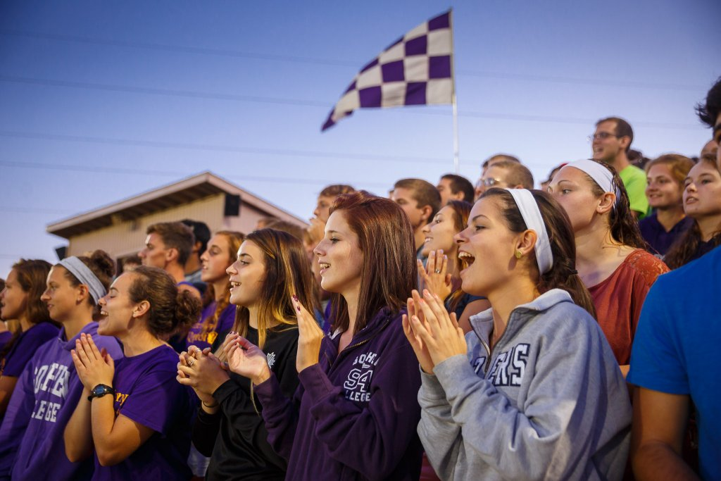 Goshen College students cheering on their classmates at a soccer game