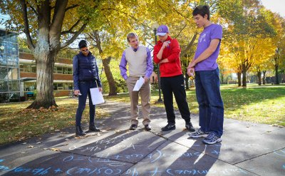 Four male students work with Professor David Houseman on equations outside on the sidewalk using chalk.