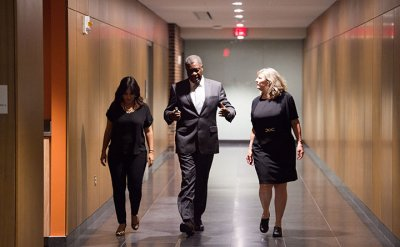 Two women and one man in business clothes walking down a vacant hallway.