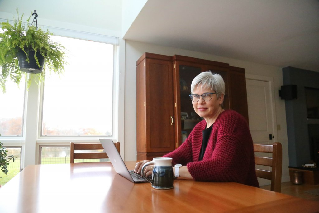 President Stoltzfus sitting at her kitchen table while working on her laptop with coffee near by